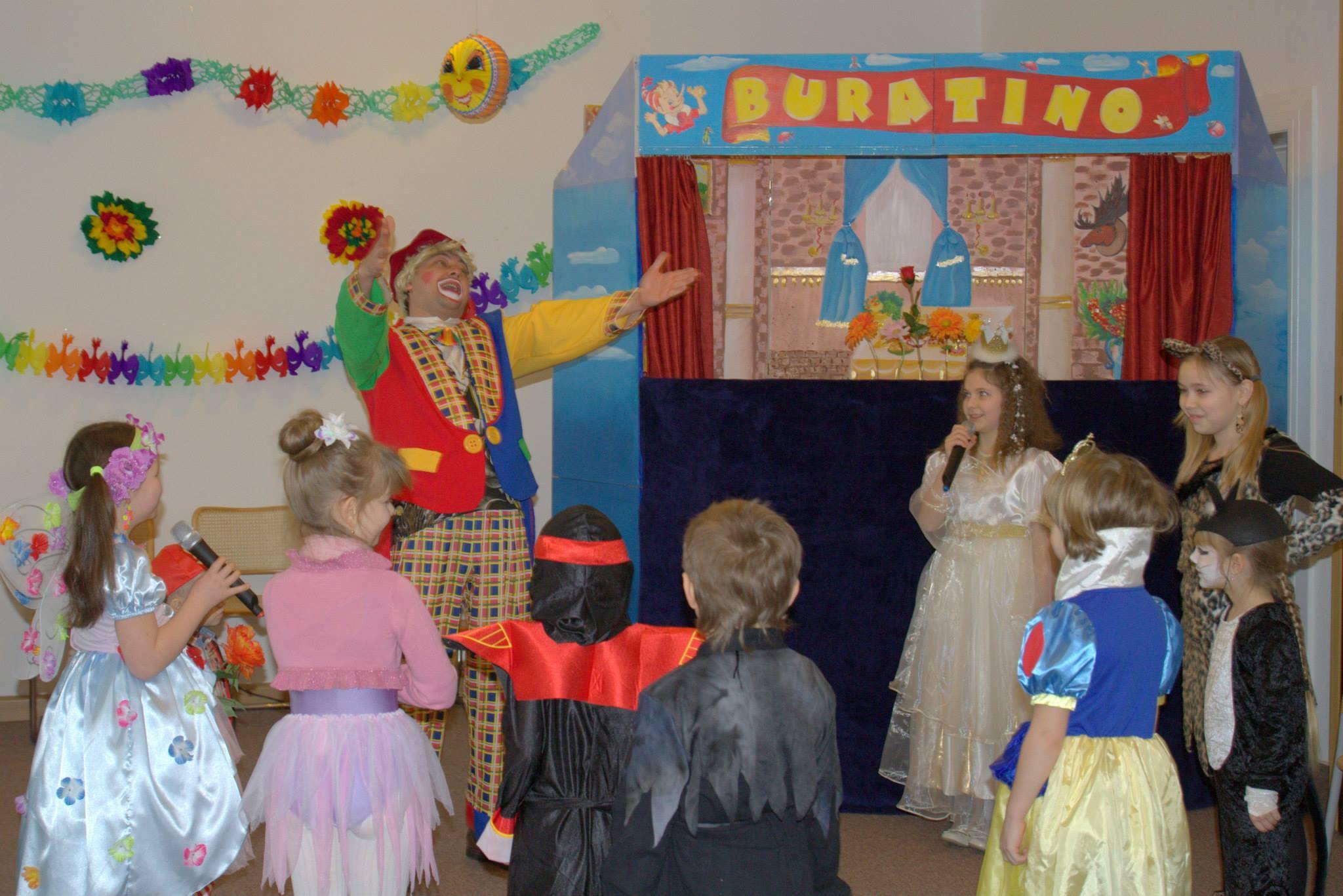 Foto Aufführung Puppentheater Buratino, mit spielenden Kindern und Clown Fulik