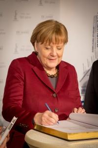 Angela Merkel trägt sich in das Goldene Buch des Stadt Leuna ein.