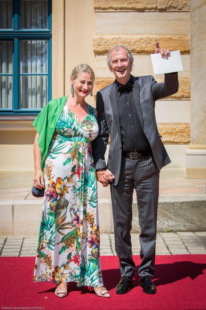 Актер Питер Прагер в сопровождении спутницы в экзотическом летнем платье