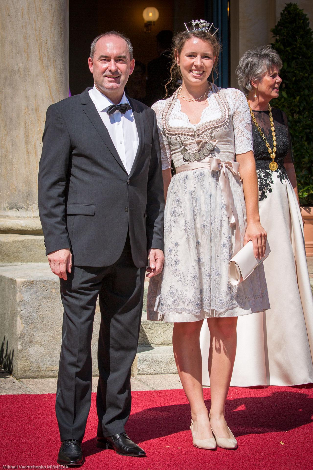 """Хьюберт Айвангер, государственный министр по экономическим вопросам,  региональному развитию и энергетике Баварии, с королевой """"Хмеля""""  Халлертау Катариной Майер в дирндле и с маленькой короной"""